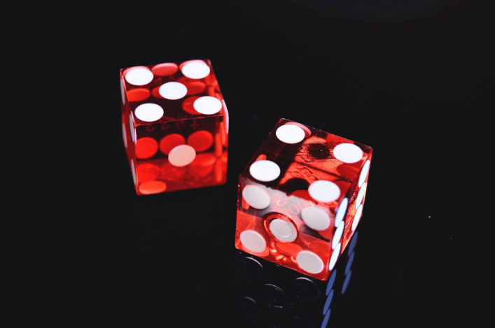 tow red dices on black surface